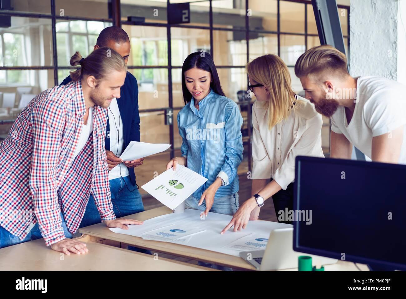 Erfolgreiches Team. Gruppe junger Geschäftsleute arbeiten und miteinander kommunizieren im Creative Office. Stockbild