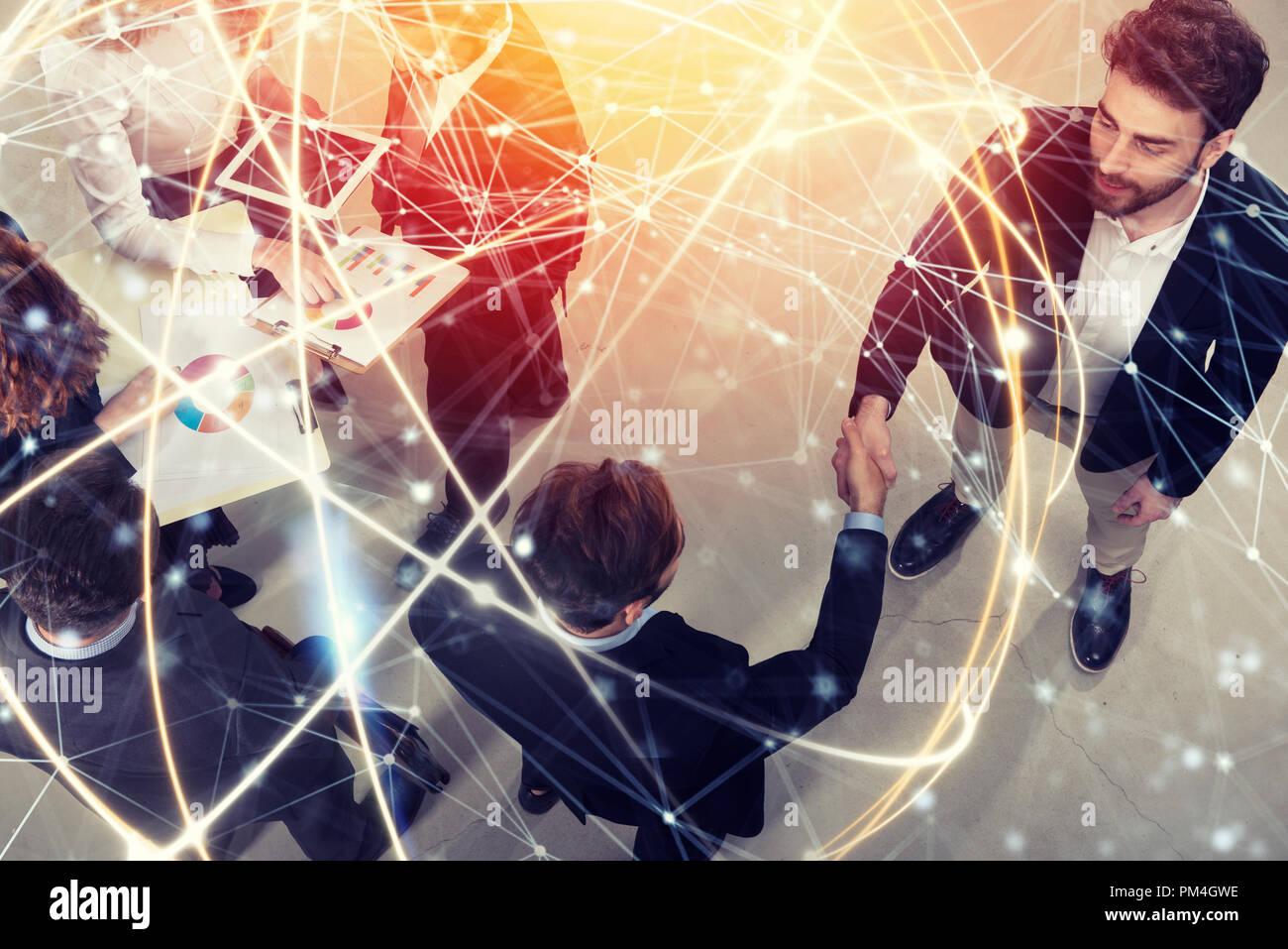 Handshaking business Person im Büro. Konzept der Teamarbeit und Partnerschaft. Double Exposure mit Netzwerkeffekten Stockbild