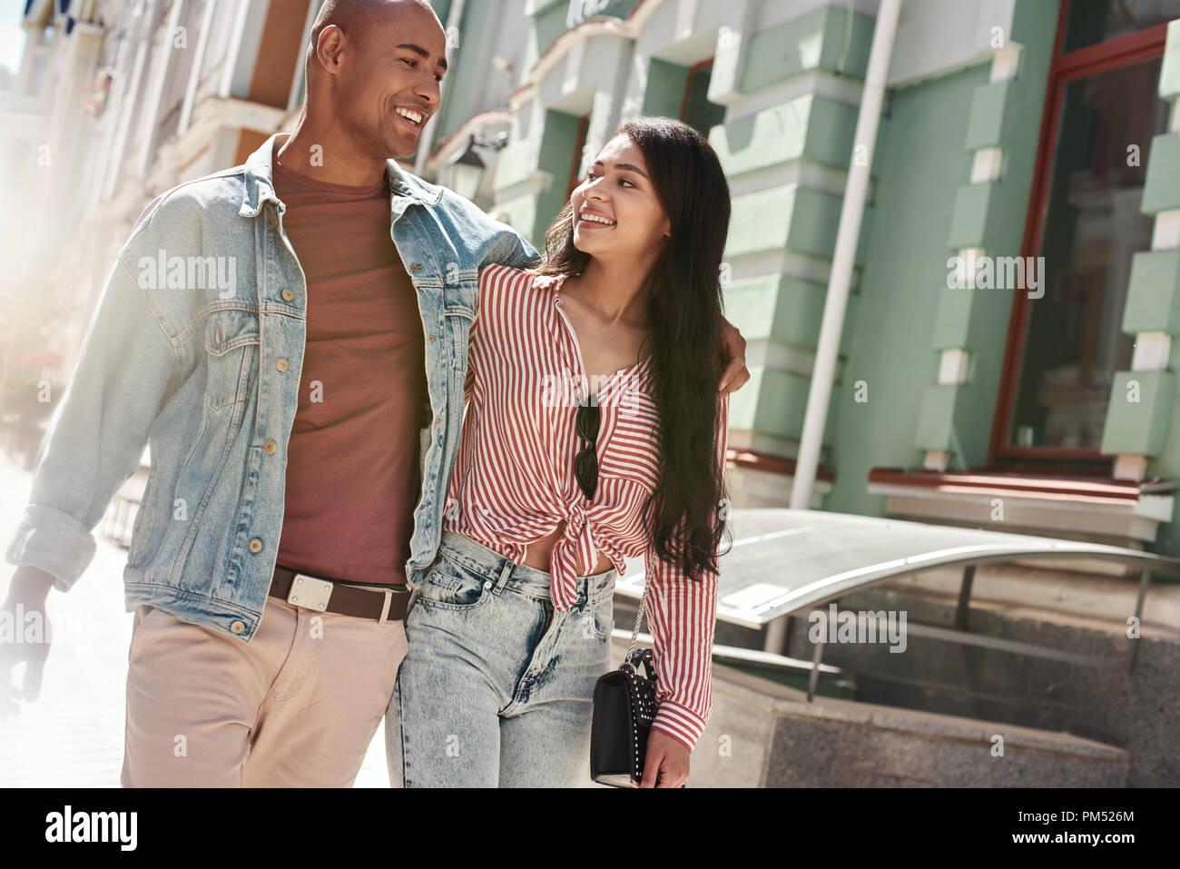 Romantische Beziehung. Junge diverse Paar zu Fuß auf der Straße umarmen sich einander reden Lächeln glücklich Stockfoto