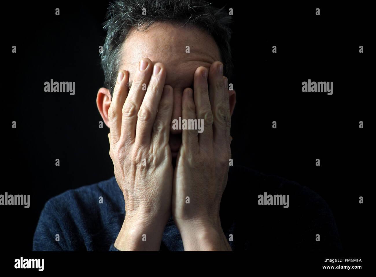 Porträt des Menschen auf schwarzem Hintergrund, betonte, die Hände auf das Gesicht Stockfoto