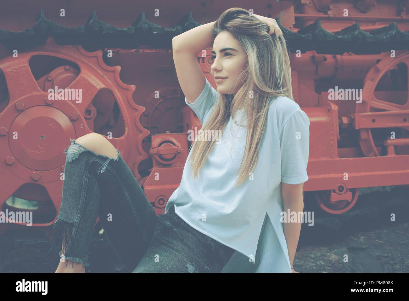 c01b6ef9b281 Eine junge Frau, die in einer zwanglosen eleganten zerrissene Jeans und weißem  Hemd posieren auf