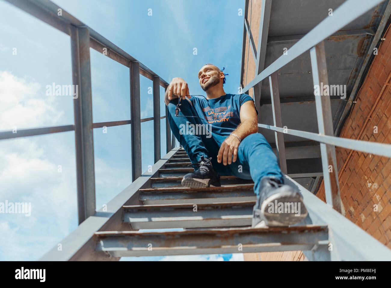 Jungen attraktiven Mann mit blauen Dreadlocks sitzen auf der Treppe. Stockbild