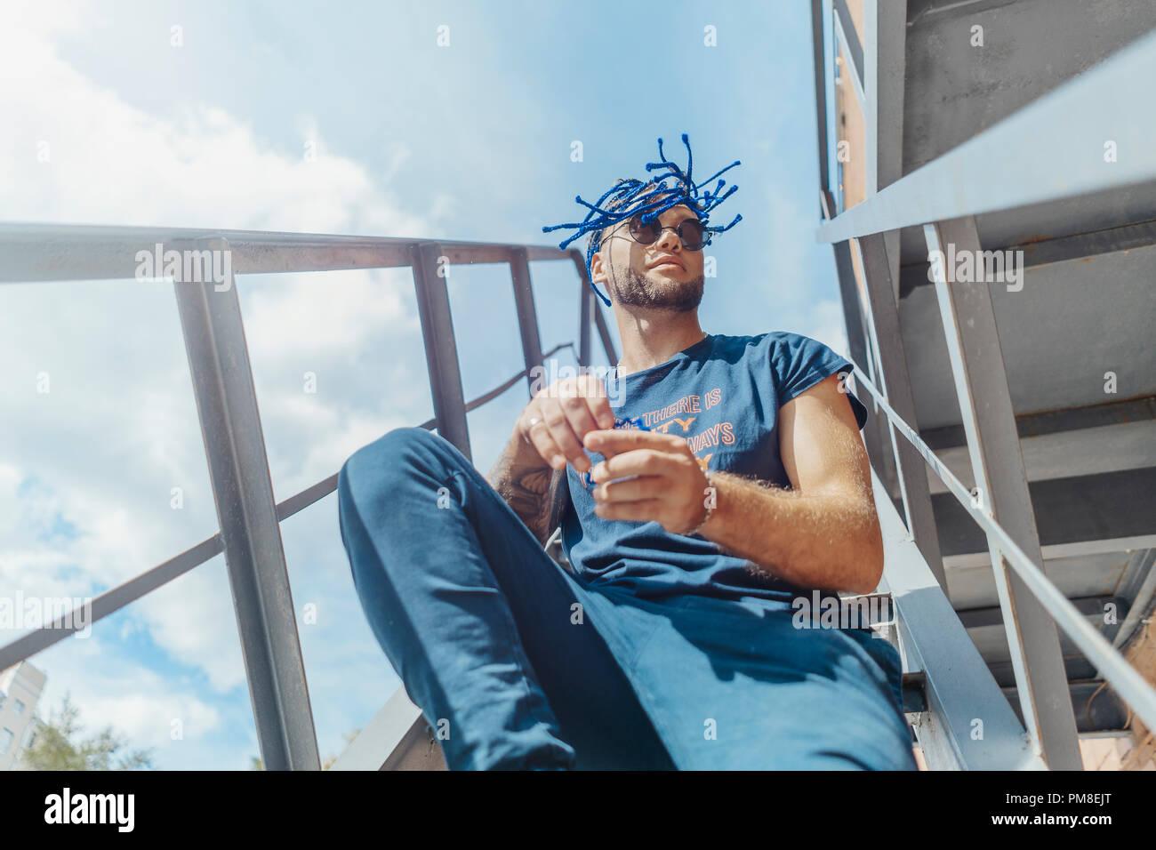 Jungen attraktiven Mann mit blauen Dreadlocks sitzen auf der Treppe und schüttelte seine Haare. Stockbild