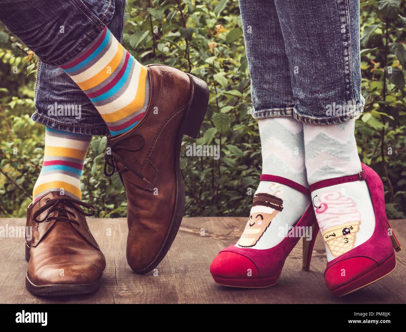 a4413c1262b2 Männer und Frauen Füße in schicke Schuhe, helle, farbenfrohe Socken mit  Streifen Muster und Bilder von Eis auf der Holzterrasse im backgroun