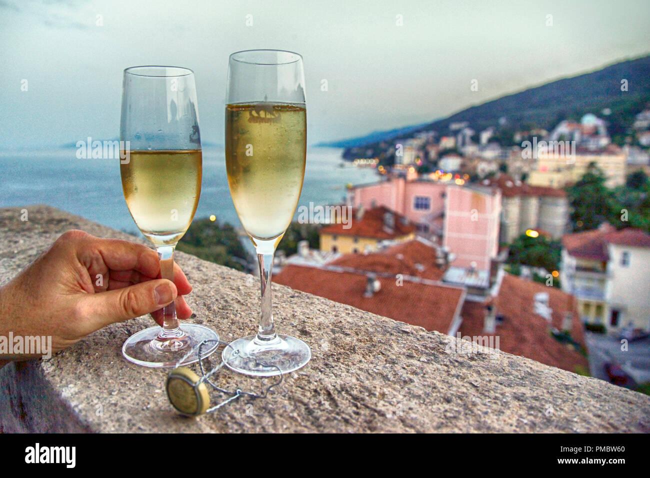 Zwei gefüllte Champagnergläser mit eines Menschen Hand ein Glas auf einem Balkon mit Blick auf das Dorf und die Adria in Kroatien Holding Stockfoto