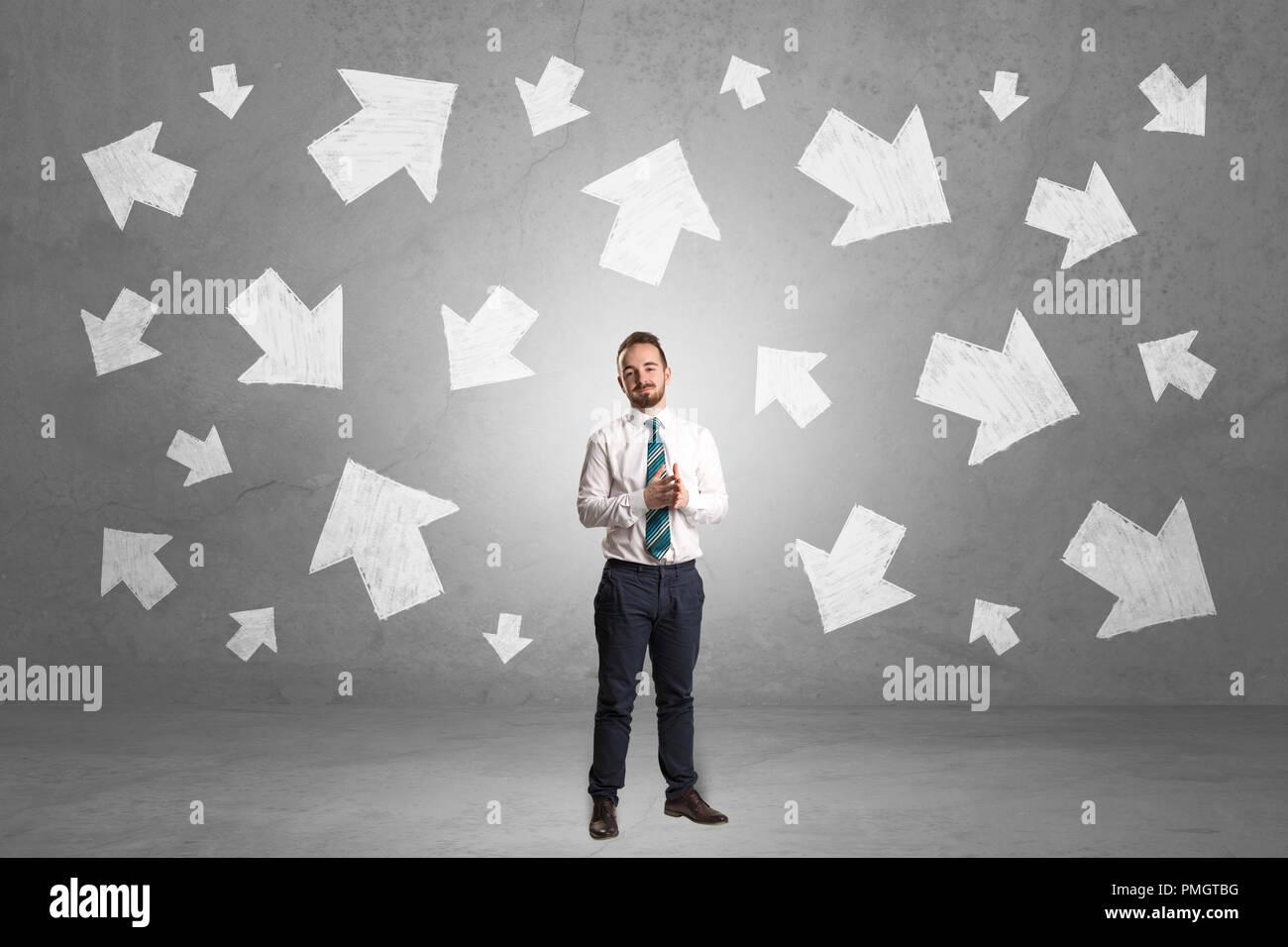 Gut aussehender Geschäftsmann stand vor einer Wand mit Kreide gezeichnet Pfeile Stockbild