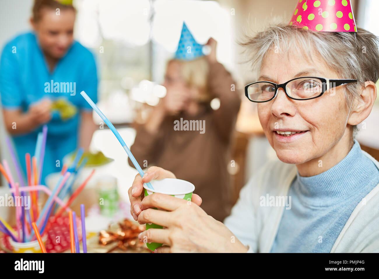 Ältere Frau im Seniorenheim feiert Geburtstag mit Freunden und der Familie Stockbild