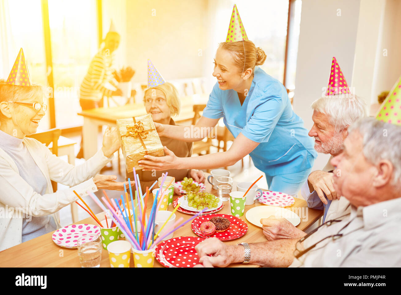 Senioren feiern Geburtstag zusammen im Seniorenheim mit Kuchen und Geschenk Stockbild