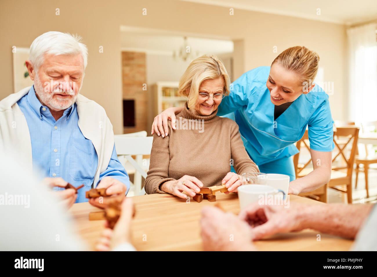 Fürsorgliche Betreuer Kümmert Sich Um Die Senioren Spielen Mit Dem