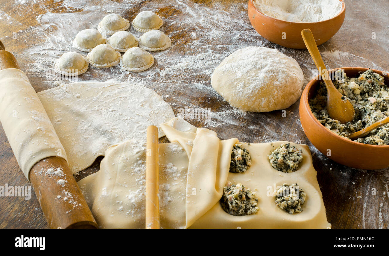 Die hausgemachten Nudeln: Der Teig zubereitet und geknetet, gefüllt mit Käse, Ricotta, Mangold und Schinken, große runde Ravioli (Sorrentino) vorbereitet und lesen Stockbild
