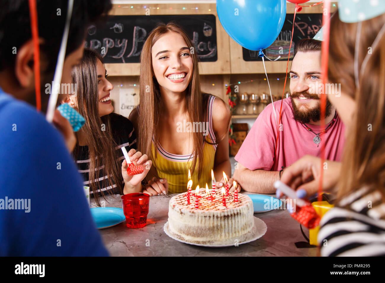 Brünette lange Haare Mädchen sitzen um ihre Freunde und lächelnd viel auf eine Geburtstagsfeier Stockbild