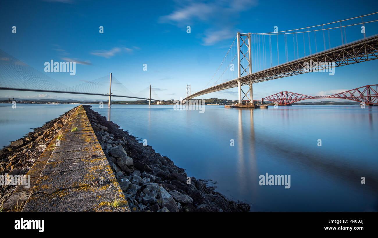 Die drei her Brücken sind ein beeindruckender Anblick, wie sie über die Firth-of-Forth, sowie Straßen- und Schienenverkehr links in Edinburgh Stockbild