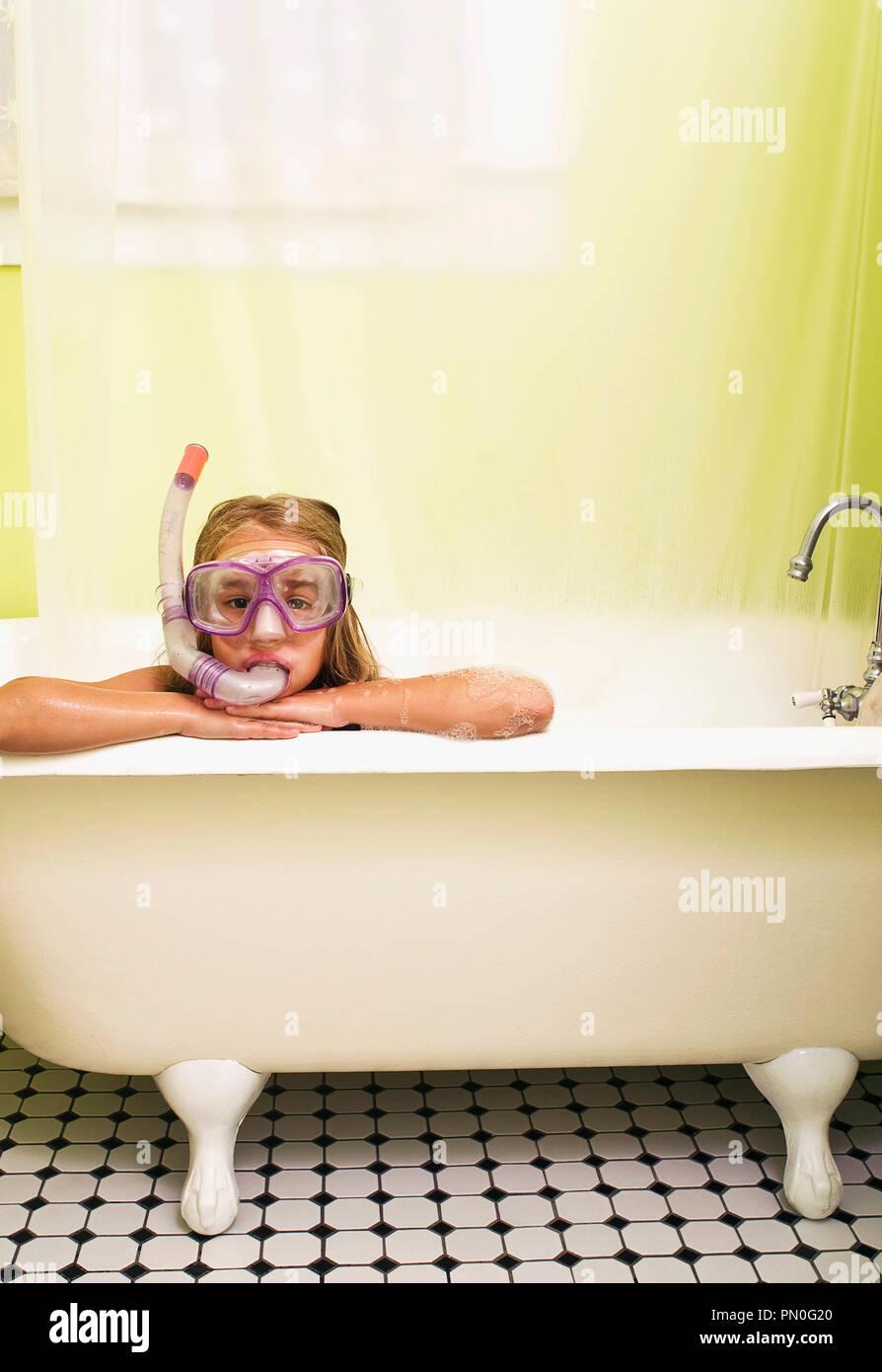 Ein junges Mädchen in einer Badewanne mit Schnorchel in den Mund. Stockbild