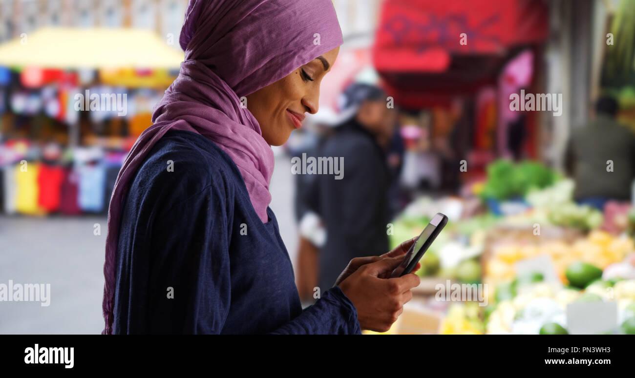 Schöne junge muslimische Frau sms mit Smartphone außerhalb Stockfoto