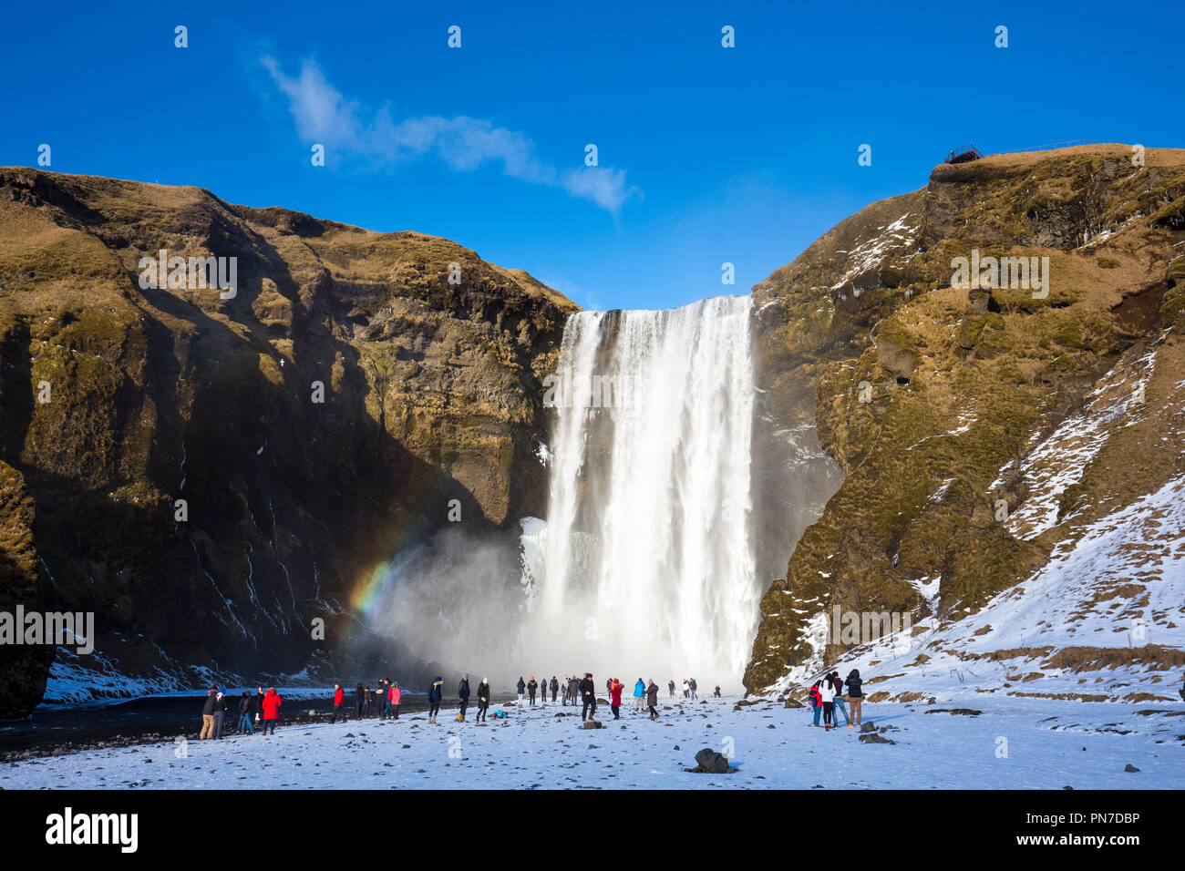 Touristen und Rainbow an spektakulären Skogar Wasserfall - skogar - im Süden Islands mit sprudelnden Gletscherschmelze Gewässern Stockbild
