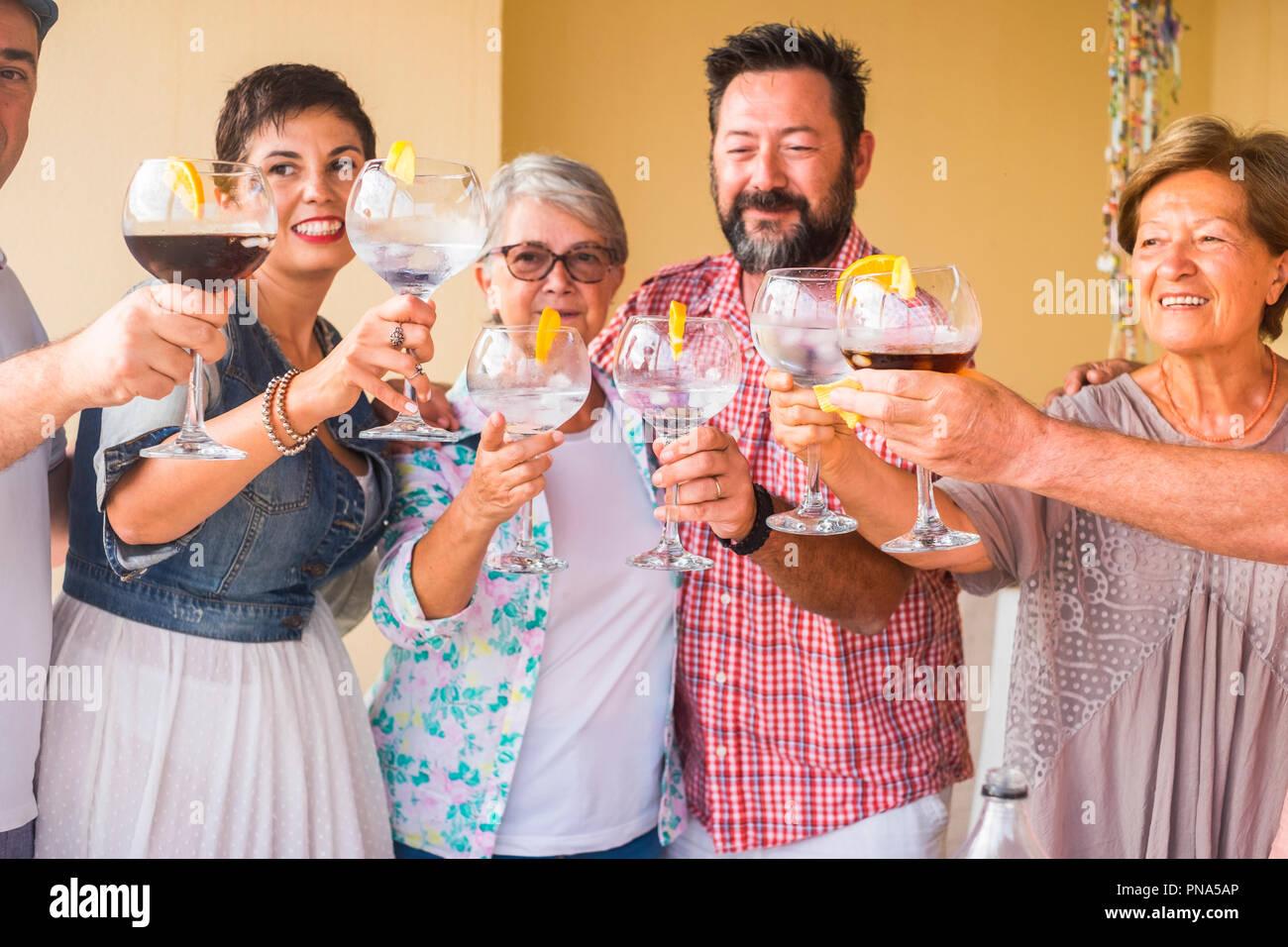 Glückliche Gruppe unterschiedlichen Alters Menschen feiern und Spaß haben, in Freundschaft zu Hause oder im Restaurant. zujubeln und Toasten mit Cocktails und Stockbild