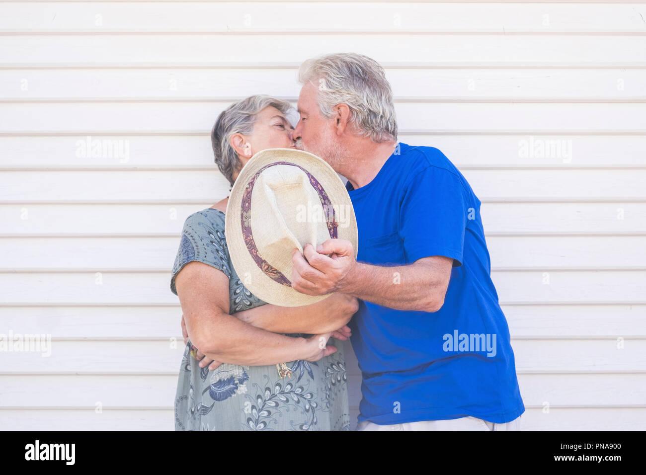 Valentinstag Konzept mit älteren Schöne senior Paar küssen Hidding mit einem beigen Hut mit weißem Holz Hintergrund Wand hinter Ihnen. Liebe und Stockbild