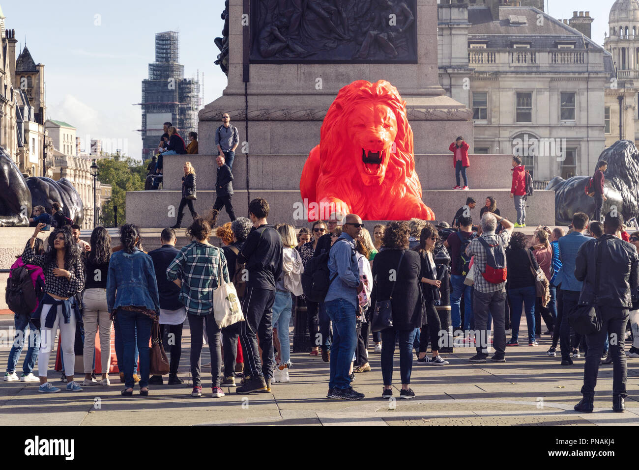 19. September 2018 - London, England. Touristen, die auf der Suche nach hellen roten, Gedicht - brüllender Löwe, die vor kurzem in Trafalgar Square enthüllt. Stockbild