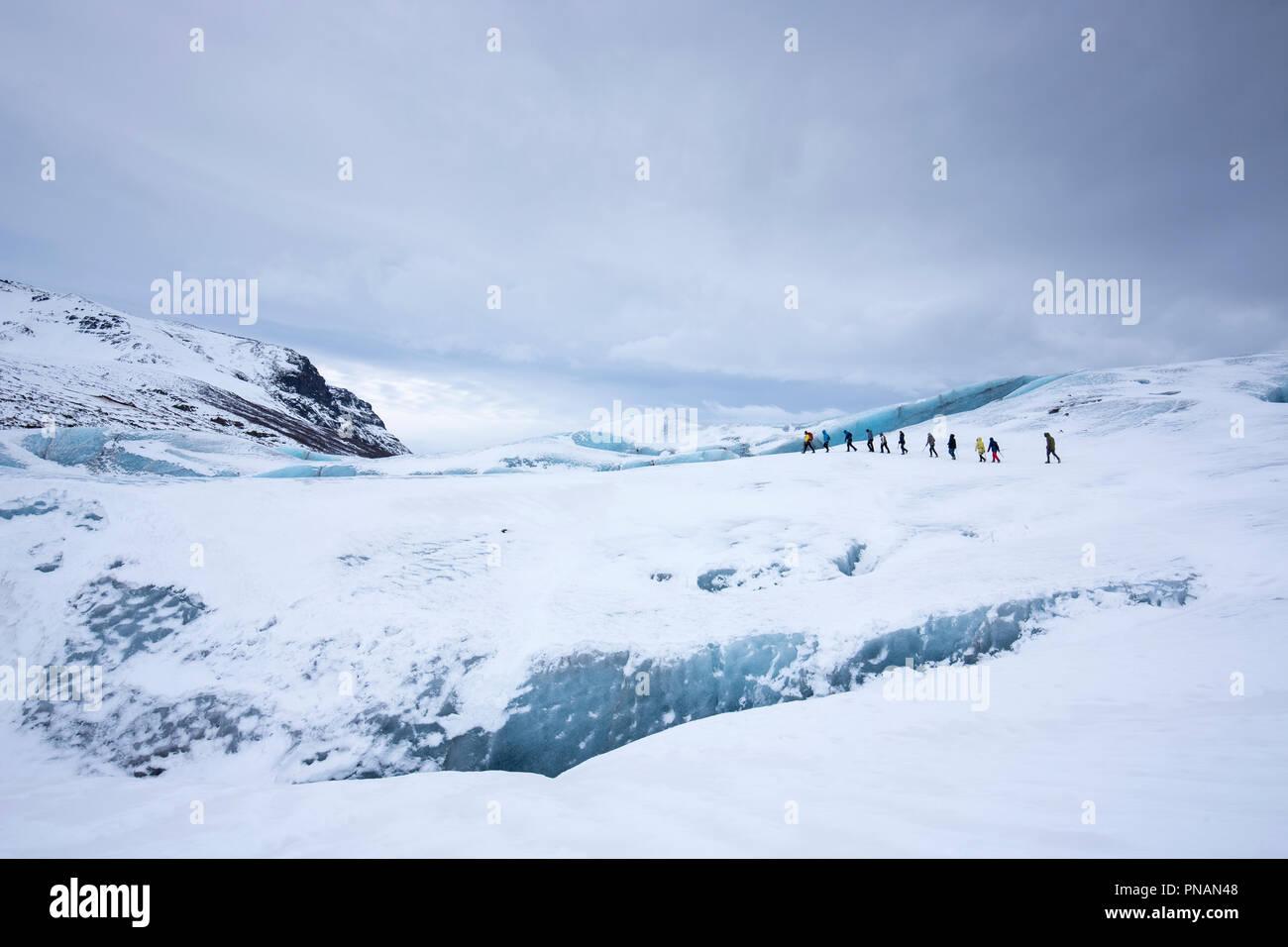 Touristen durch das Tragen von schützender Kleidung für Gletscherwanderung auf Svinafellsjokull Gletscher eine Steckdose Gletscher Vatnajökull, South Island Stockbild