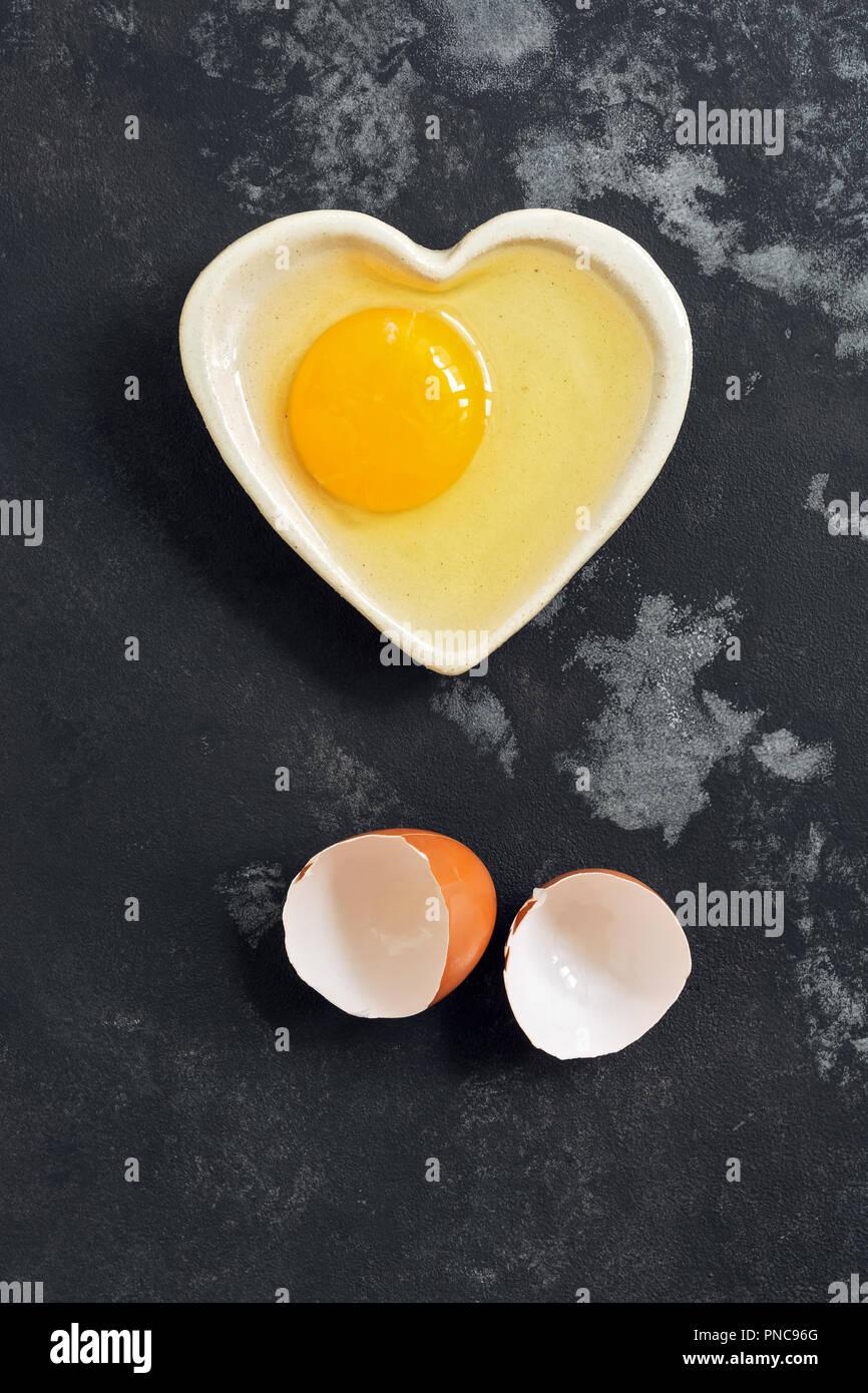 Rohes Ei in eine Schüssel geben und Eierschale auf einem dunklen konkreten Hintergrund gebrochen. Flach. Stockbild