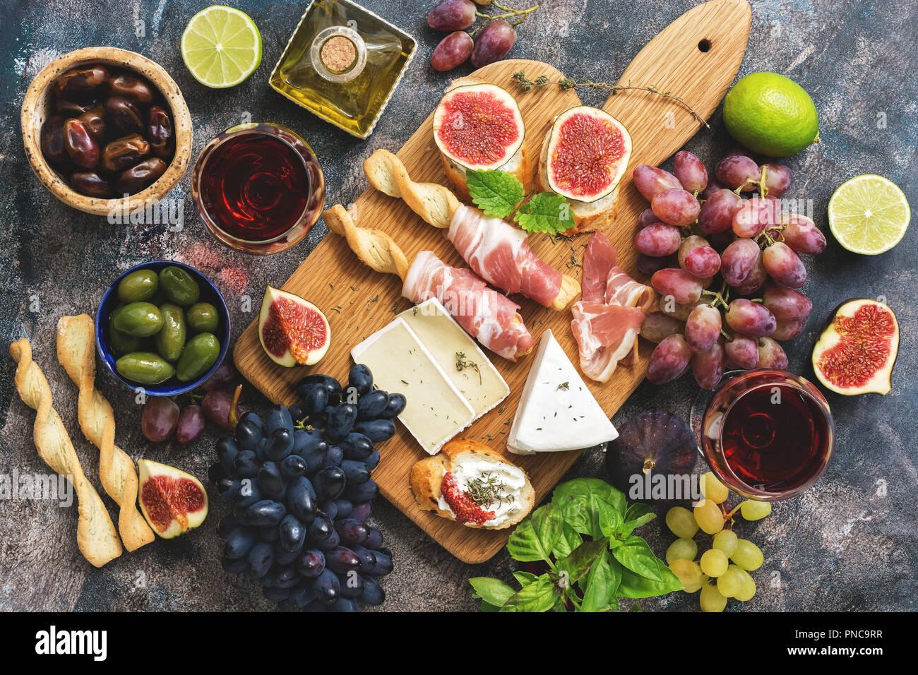 Eine Vielzahl von Snacks, Prosciutto, Trauben, Wein, Käse mit Schimmel, Feigen, Oliven auf einem urigen Hintergrund. Ansicht von oben, flach Stockbild