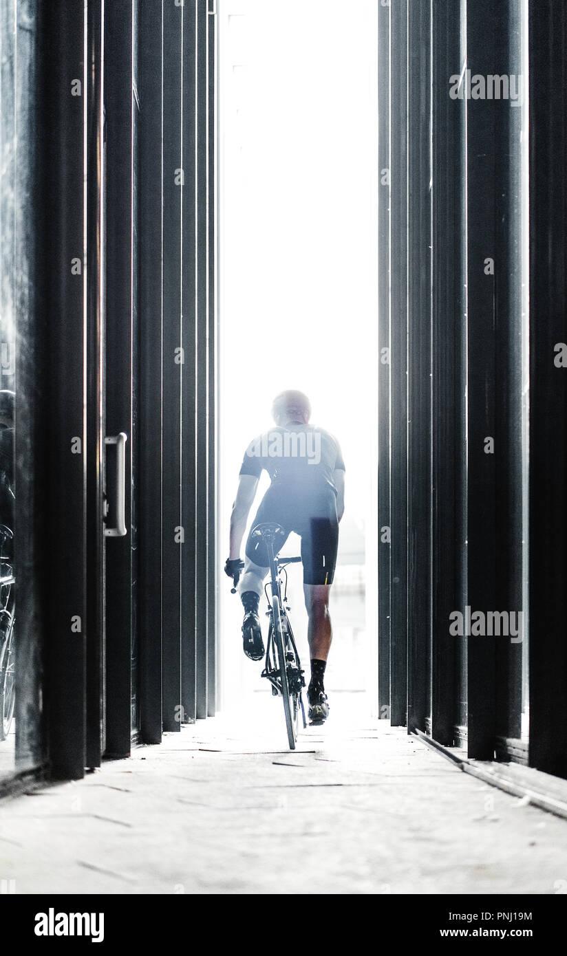 Sport bike Mann reiten in städtischen gläserne Tunnel mit Licht. Stockbild