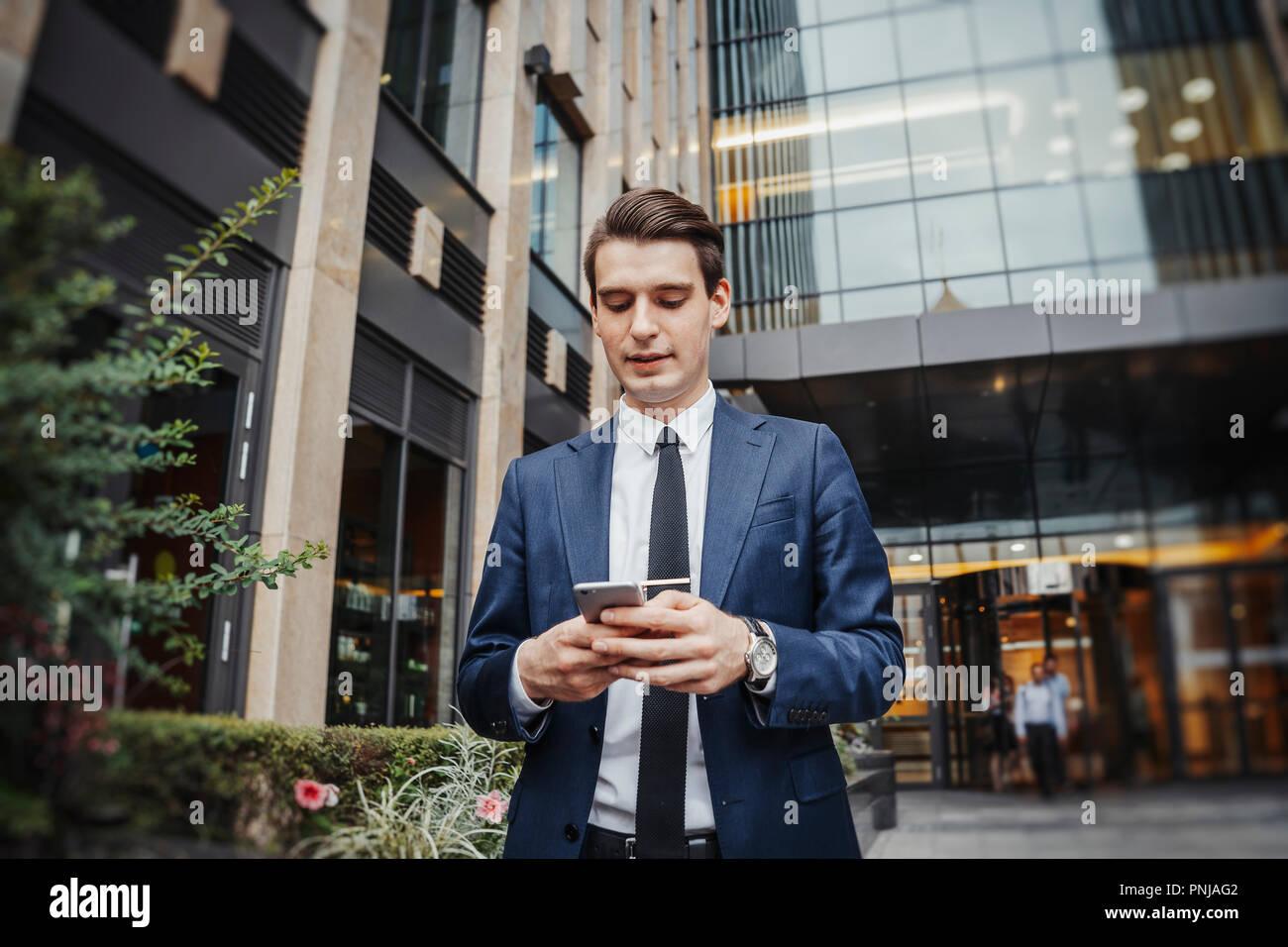Nahaufnahme von Geschäftsmann neben Wolkenkratzer auf dem Bildschirm des Mobiltelefons. Stockbild