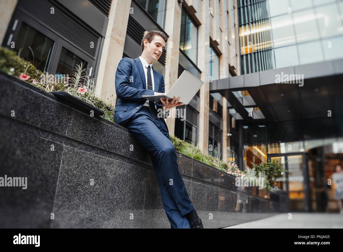 Geschäftsmanns, der auf dem Laptop neben Wolkenkratzer der Innenstadt. Stockbild