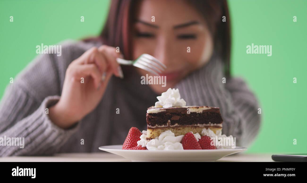 Asiatische Frau Essen Lecker Kuchen Auf Green Screen Stockfoto Bild
