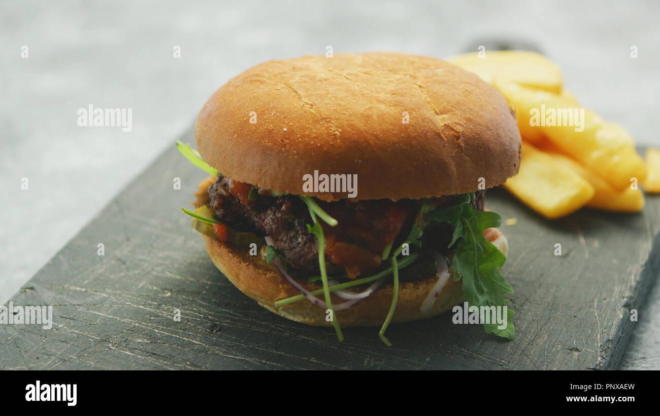 Saftige leckere Burger auf Platte Stockbild