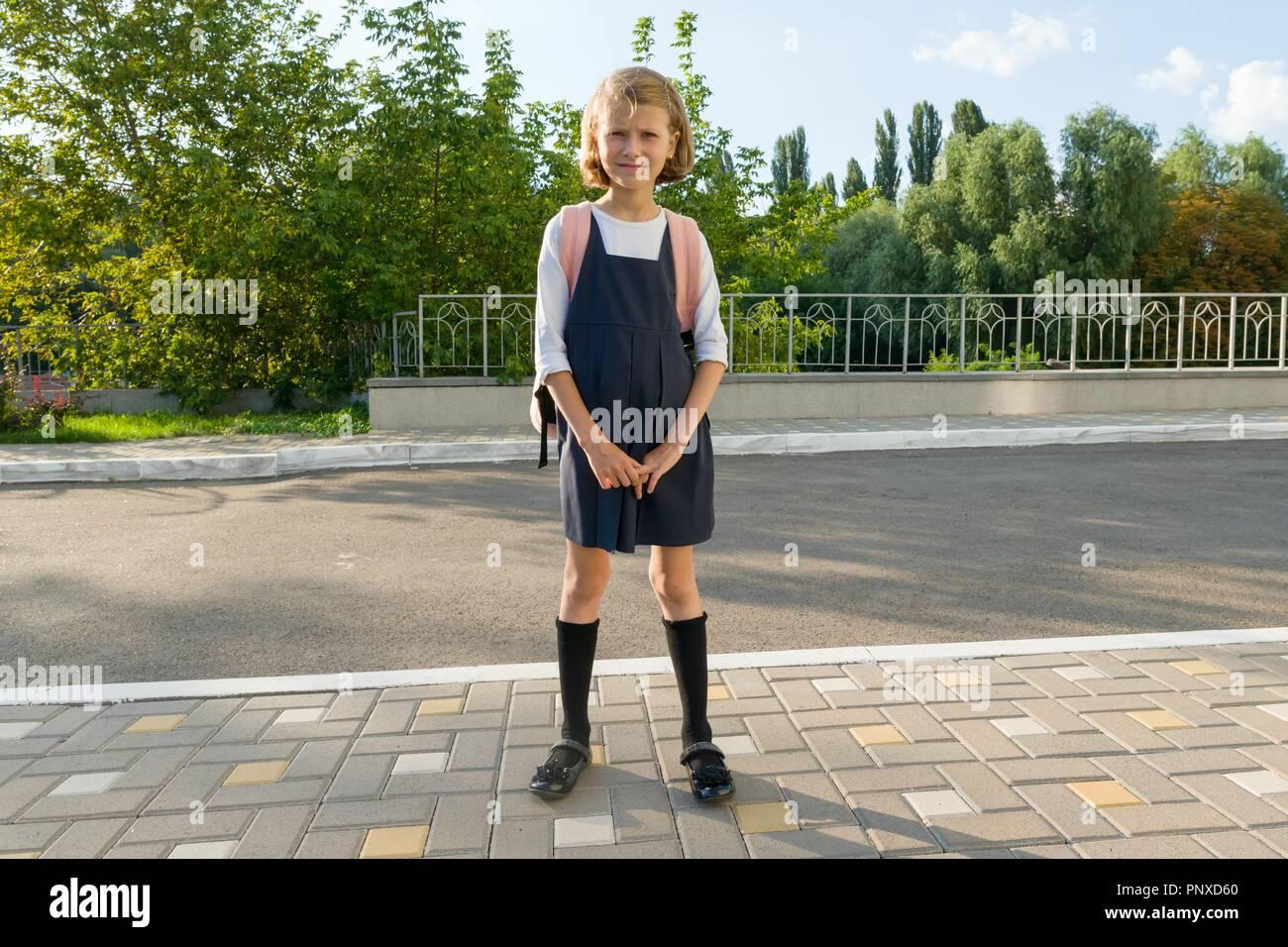 Outdoor Portrait eines kleinen Schüler, Mädchen mit Brille, Uniform mit Rucksack. Schule, Bildung, Wissen und Kinder Stockbild