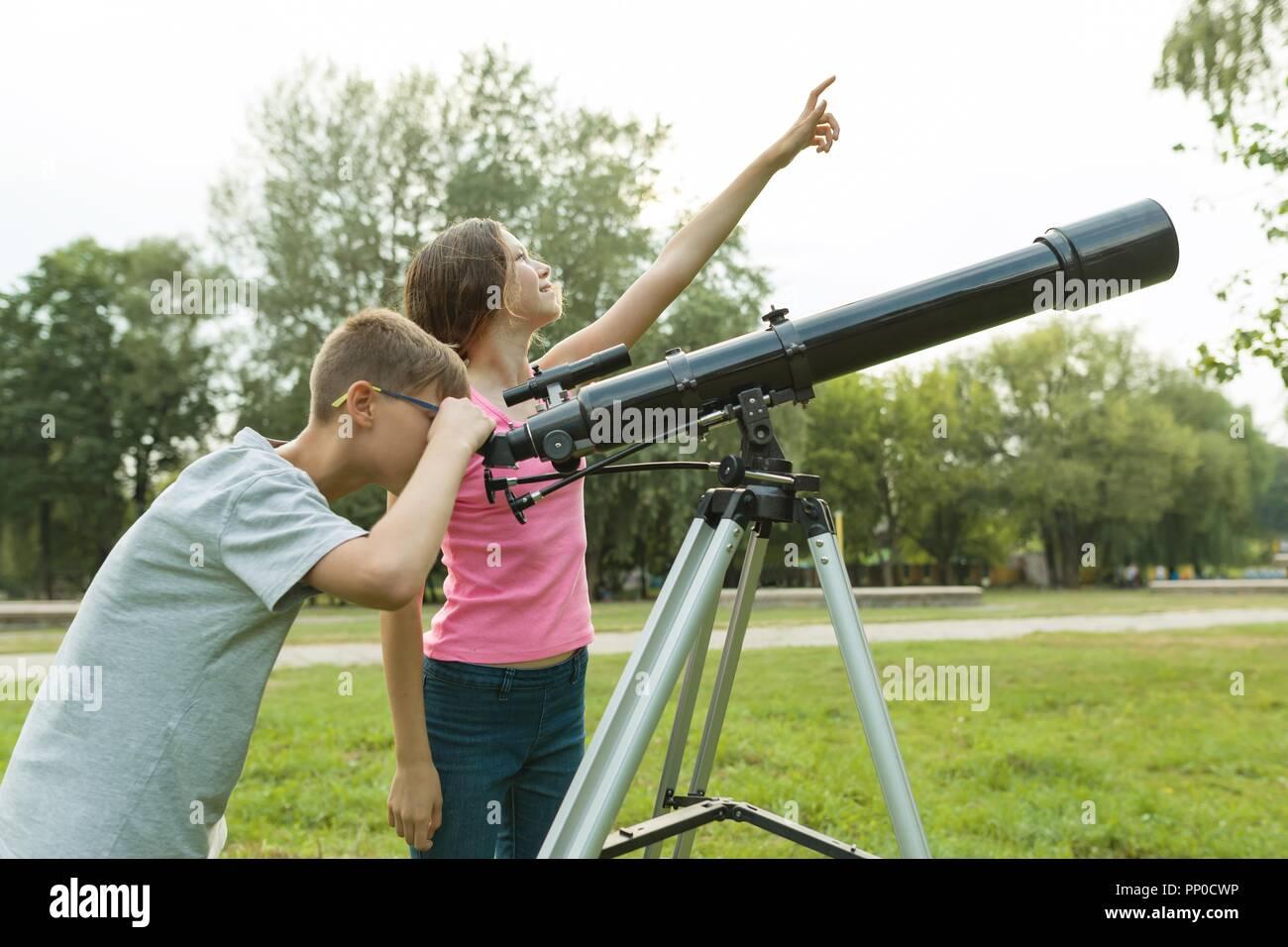Kinder und jugendliche mit einem teleskop schauen sie in den