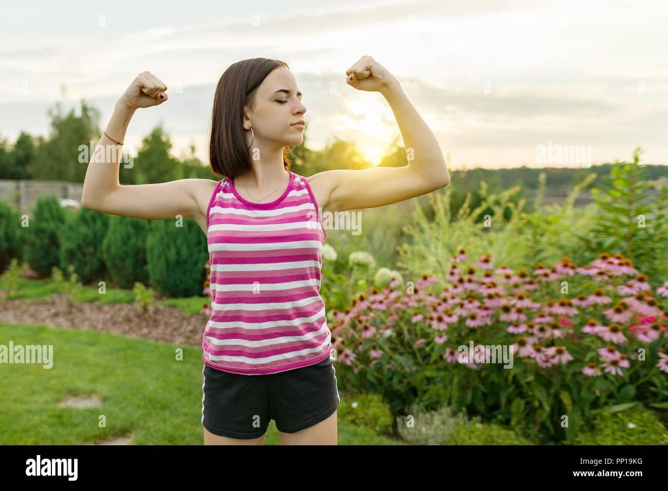 Menschen, Kraft, Ausdauer, Stärke, Gesundheit, Sport, Fitness Concept. Outdoor Portrait smiling teenage Mädchen ihre Muskeln, Hintergrund grüne Wiese Sonne Stockbild