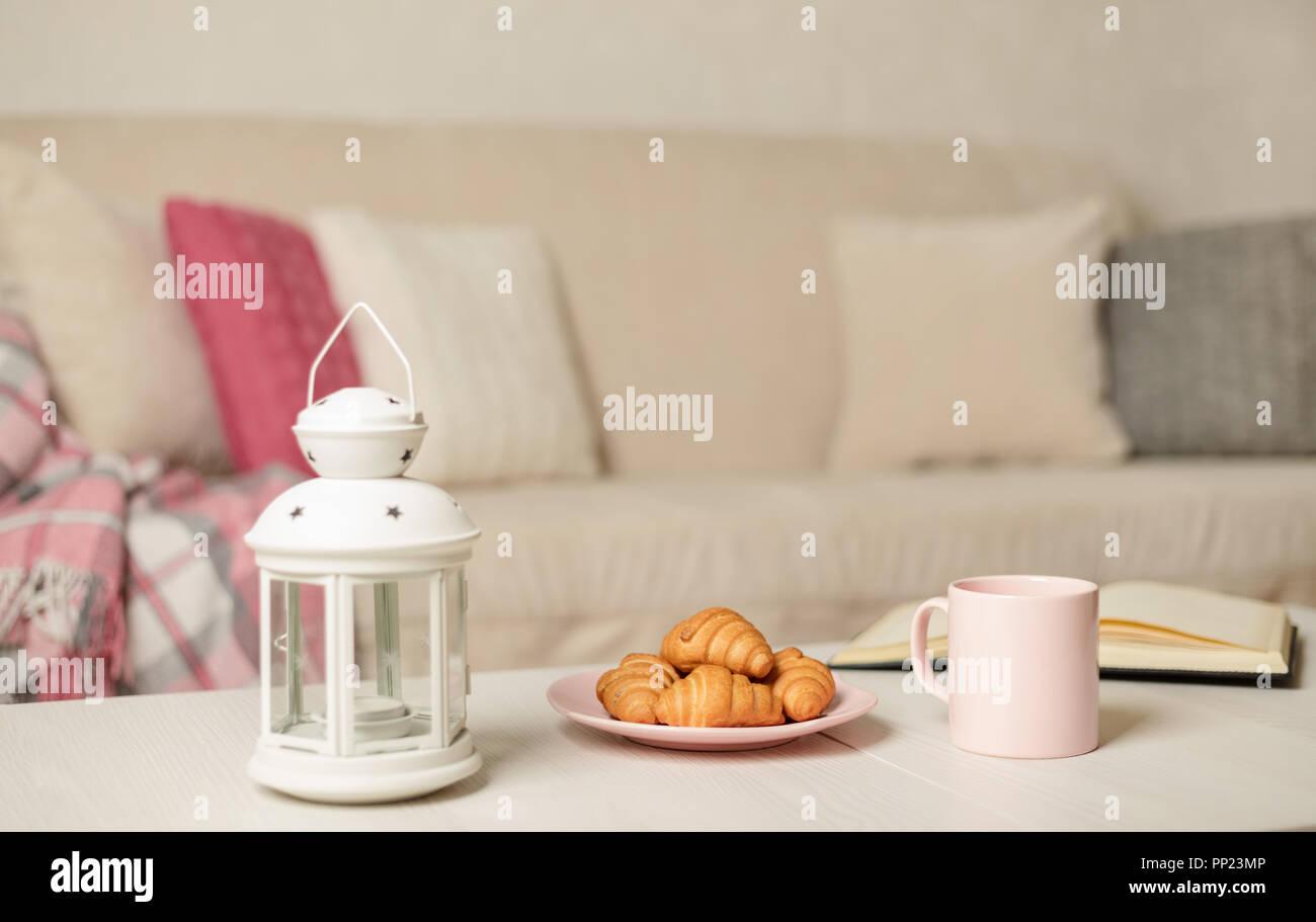 Beige Sofa mit Plaid, bunte Kissen (Rosa, Grau, Weiß) und ...