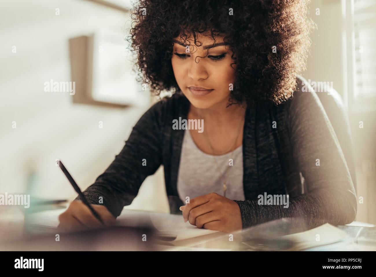 Portrait von weiblichen Architekten an Ihrem Schreibtisch arbeiten. Besetzt weibliche Designer arbeiten an neuen Gebäude planen, beim Sitzen am Tisch. Stockbild