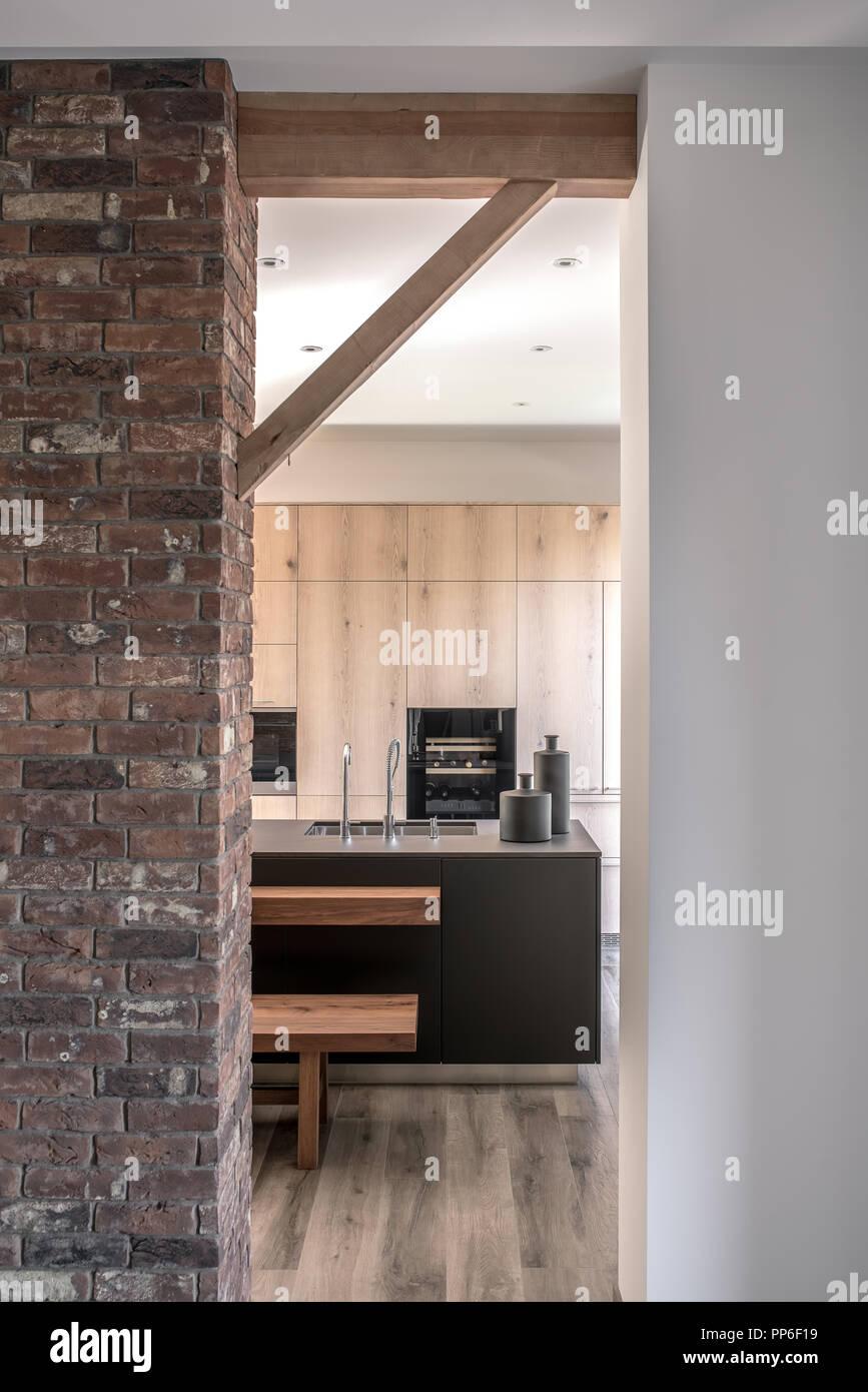 Moderne Einrichtung Mit Weißen Und Ziegelwänden Und Holzbalken. Es Gibt  Eine Küche Zone Mit Einer Insel Mit Einem Waschbecken Und Vasen, Sitzbank,  Backofen, ...