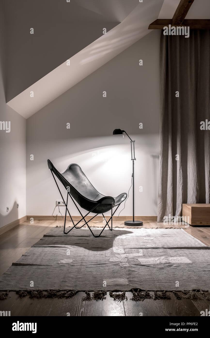 Moderne Einrichtung Mit Weißen Wänden, Holzbalken Und Parkettboden Mit  Teppichen. Es Ist Schwarz, Sessel Und Eine Leuchtende Stehleuchte, Ständer,  Vorhang.