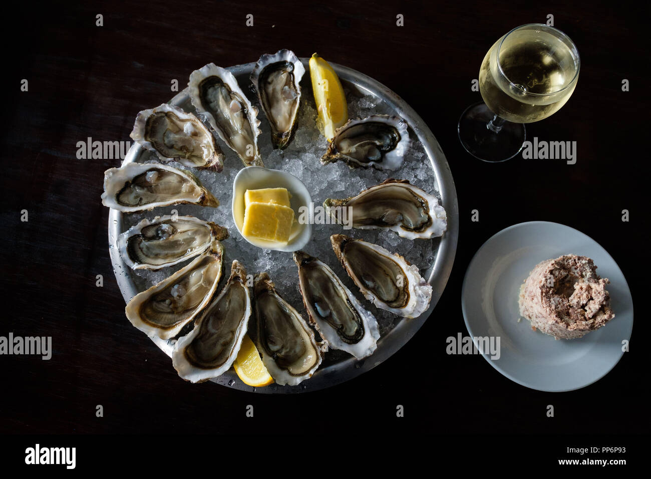 Platte der Austern aus der Bucht von Arcachon. Austern auf einem Bett aus Eis mit Zitrone, Butter, ein Glas Wein und ein paar Pastete Stockbild