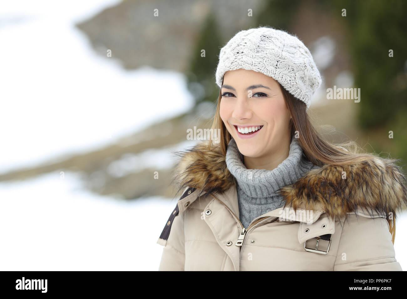 Gerne Frau posiert an der Kamera auf Winterurlaub in die schneebedeckten Berge Stockfoto