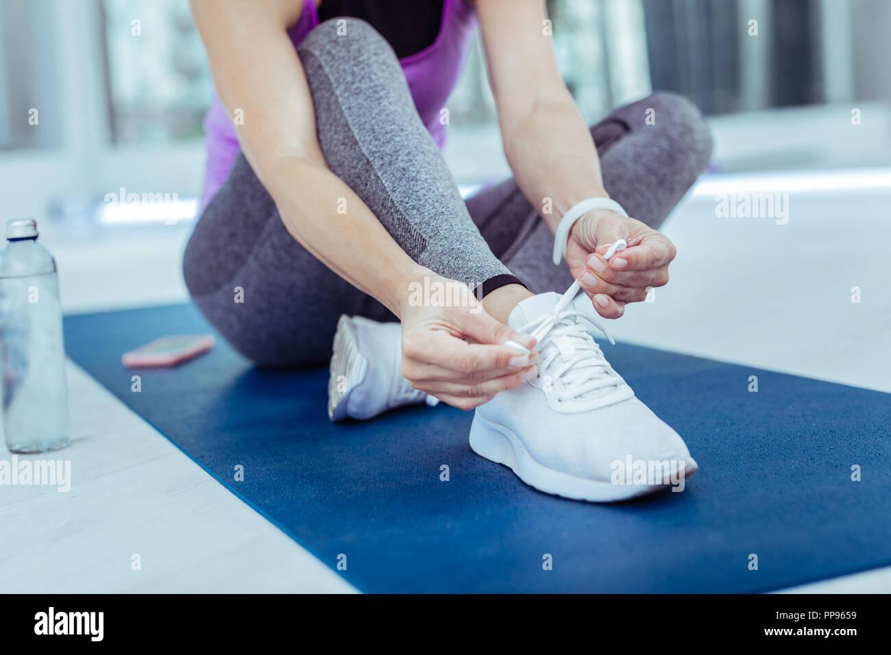 Glatte weibliche Hände binden Schnürsenkel vor dem Training Stockbild