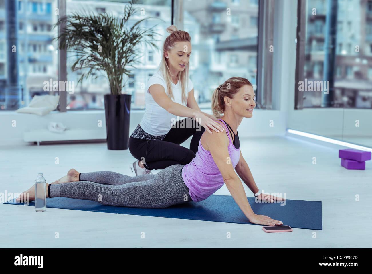 Erfahrene weibliche Trainer Korrektur frau yoga Pose Stockbild