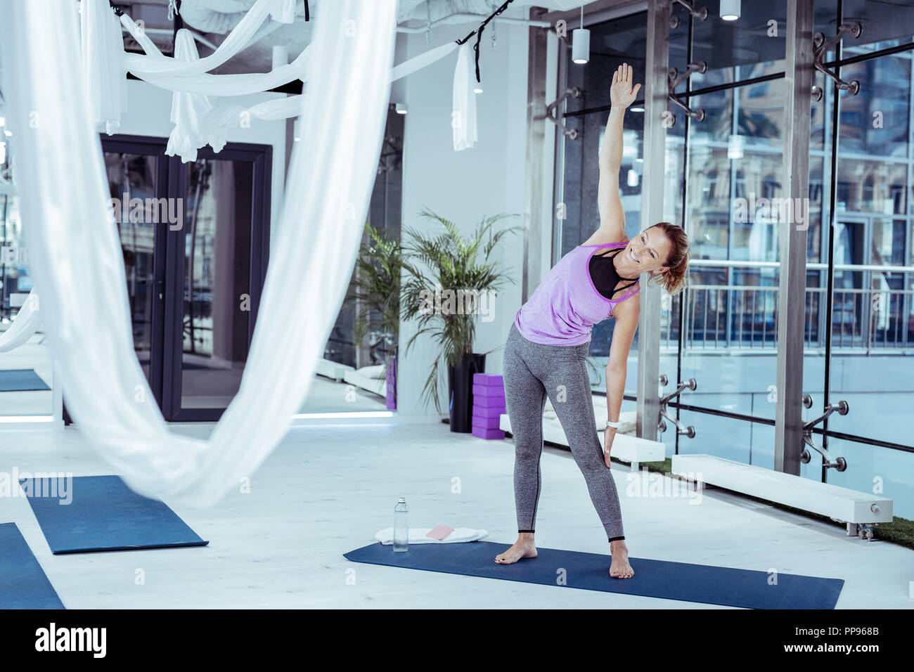 Energetische reife Frau die Kombination von Yoga-stellungen in der Turnhalle Stockbild