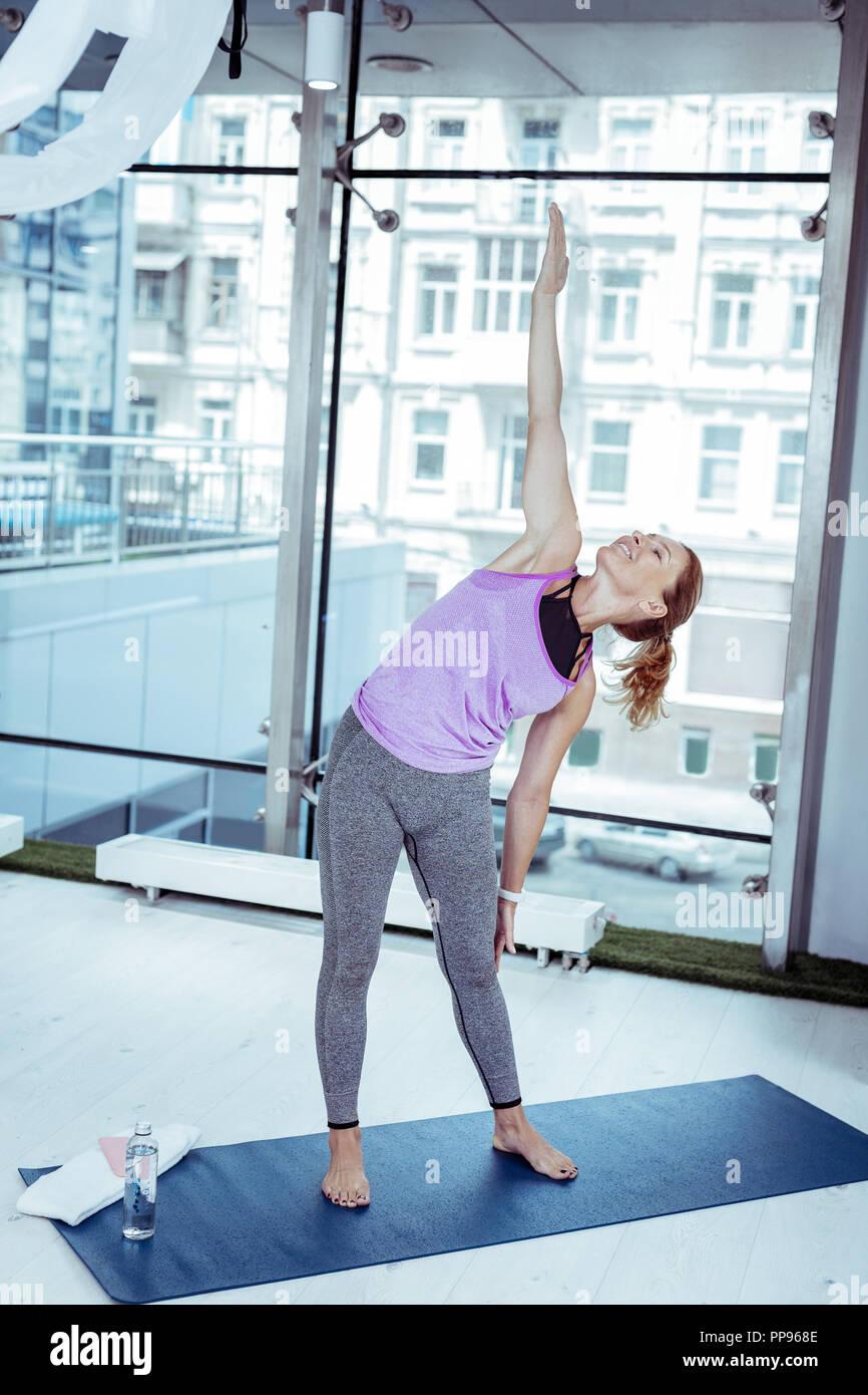 Positive reife Frau weiter Yoga üben in der Turnhalle Stockbild