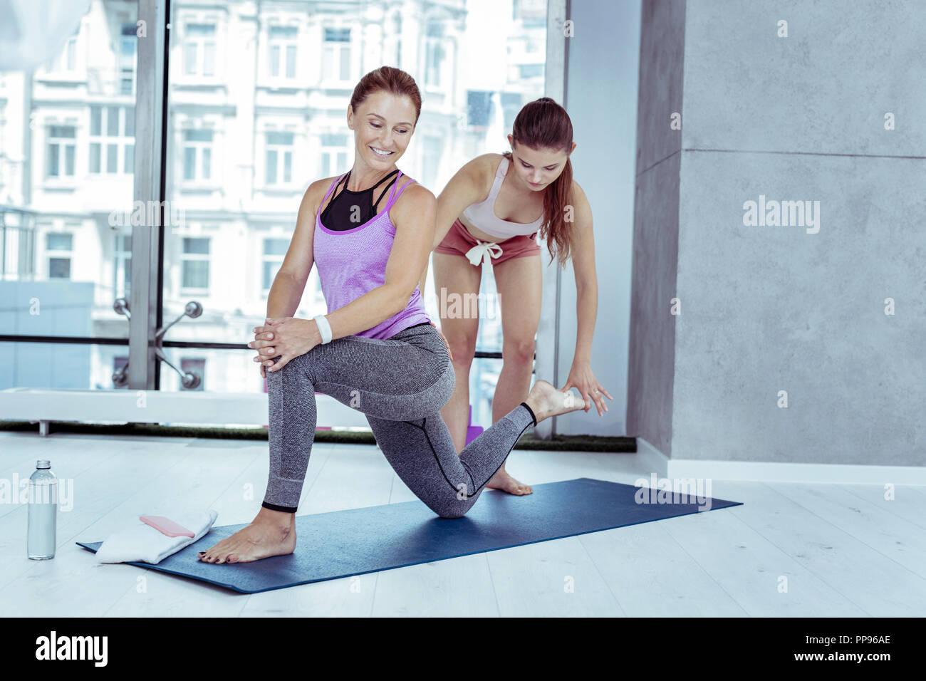 Optimistisch reife frau yoga mit Trainer Stockbild