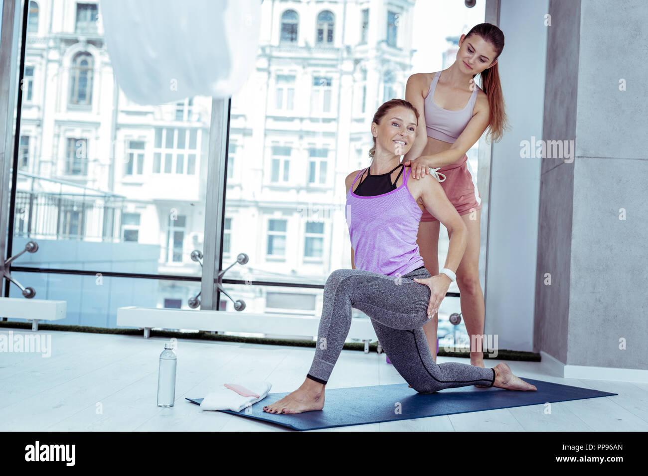 Froh, reife Frau, die in Yoga mit Trainer Stockbild