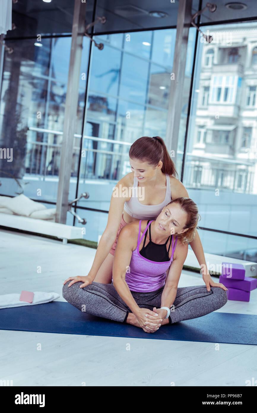 Aufmerksame reife Frau pflege Pose mit Trainer Stockbild