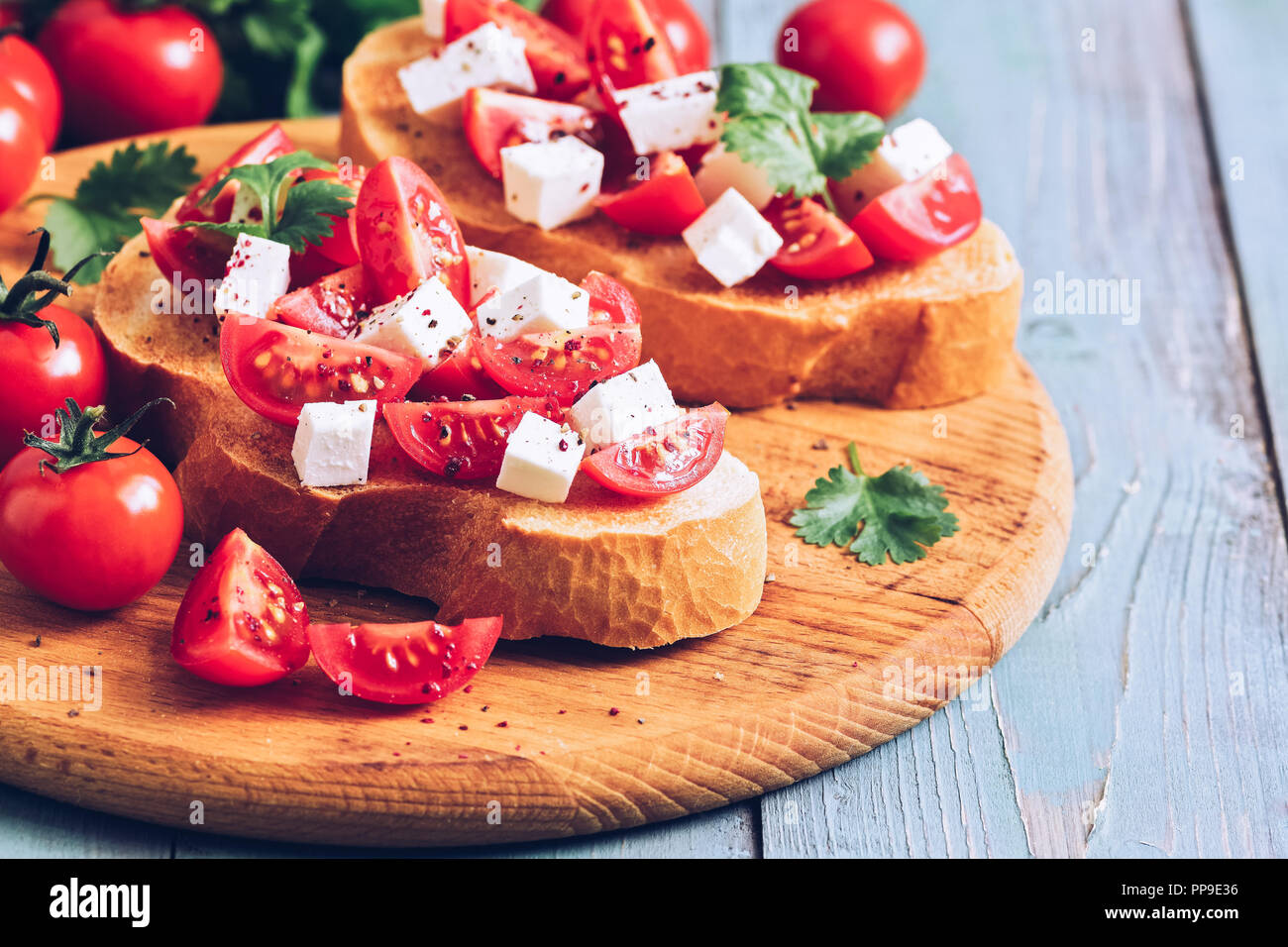 Bruschetta mit Tomaten, Käse und Grüns auf geröstetem Brot. Traditionelle italienische Küche. Selektiver Fokus Stockbild
