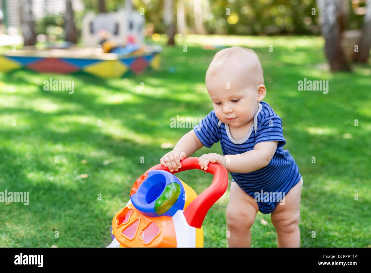 Süße kleine Jungen lernen mit Walker Spielzeug auf grünen Rasen im Hinterhof zu gehen. Baby lachen und Spaß macht ersten Schritt im Park auf hellen, sonnigen Tag im Freien. Glückliche Kindheit Konzept Stockbild