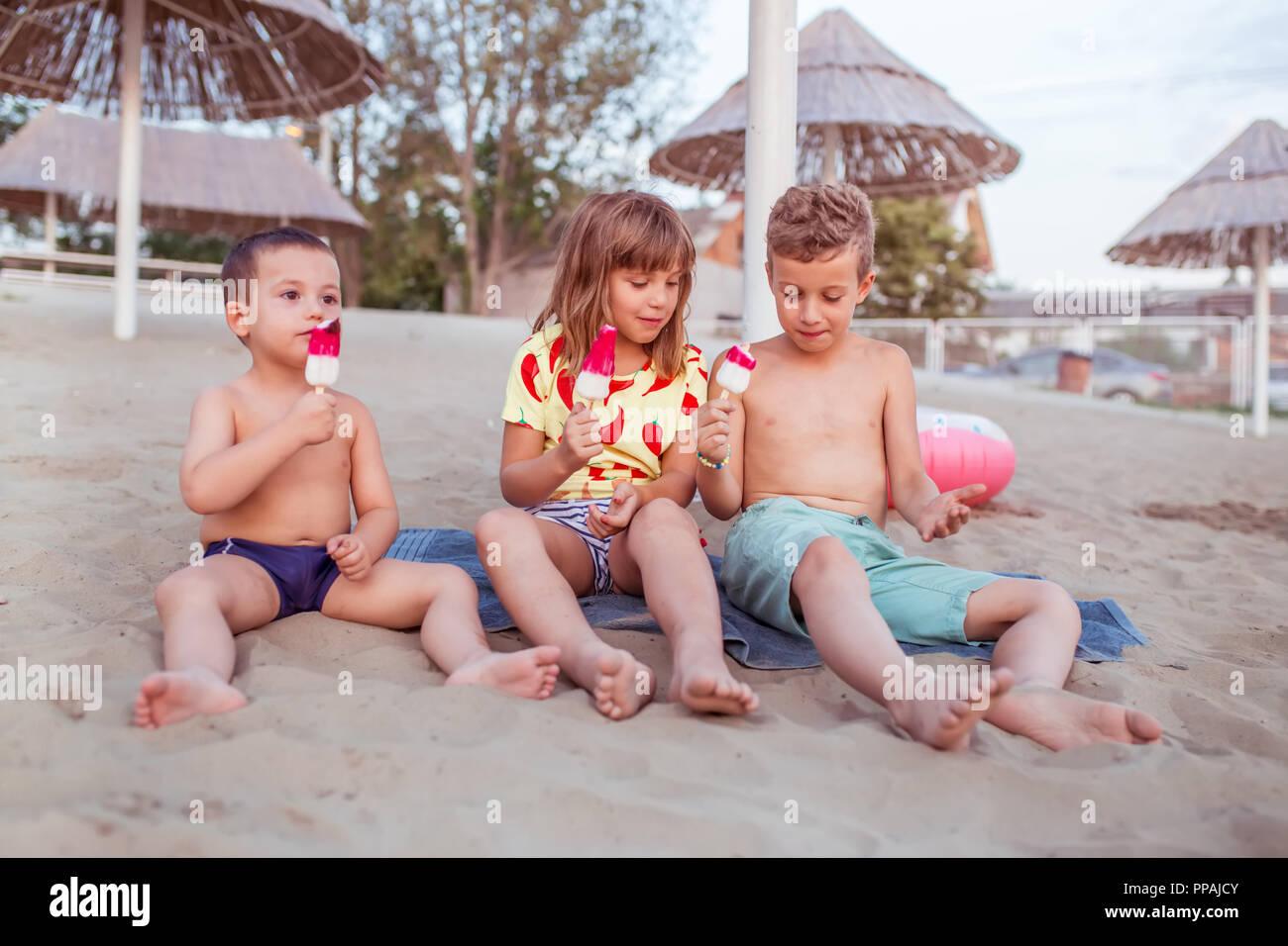 Happy positive Kinder sitzen auf dem Sandstrand und Eis essen. Menschen, Kinder, Freunde und Freundschaft Konzept Stockbild
