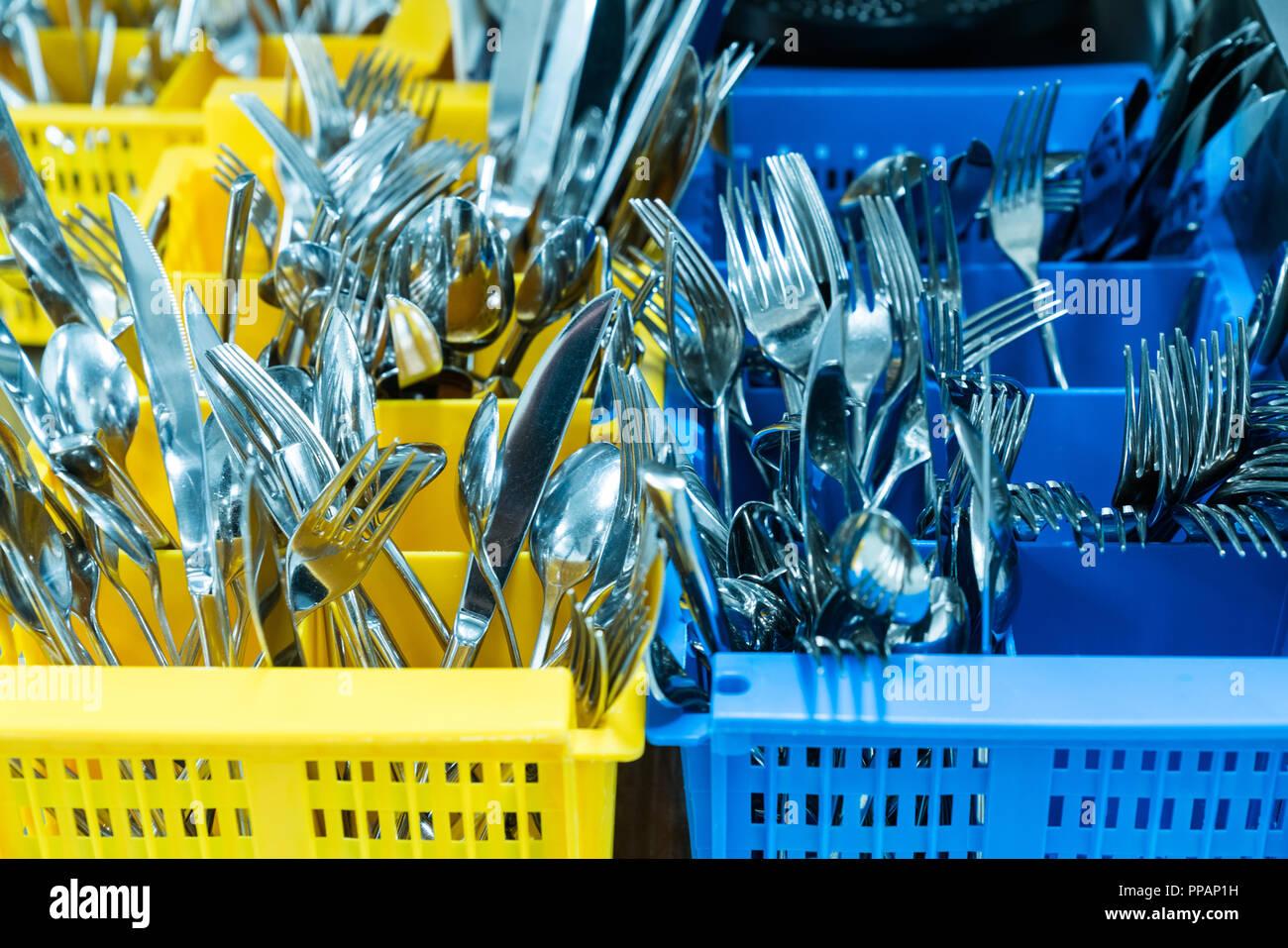 Besteck und Geschirr in bunten palstic ocntainer in einem industriellen Restaurant Küche sauber und frisch aus der Spülmaschine Stockfoto